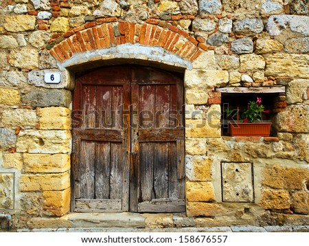 Stone house facade with old door and a small window