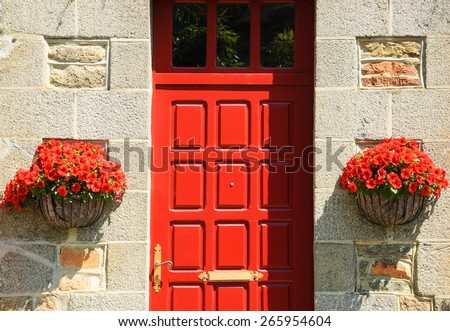 Stone house wall with red wooden door (entry to the manor's garden) and and hanging pots with red geranium flowers. Brittany, France. - stock photo