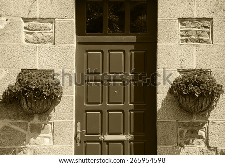 Stone house wall with wooden door (entry to the manor's garden) and and hanging pots with red geranium flowers. Brittany, France. Aged photo. Sepia. - stock photo