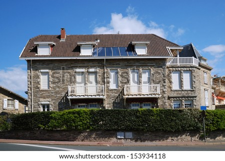 Stone house with hedge grow is in the street of  Biarritz. - stock photo