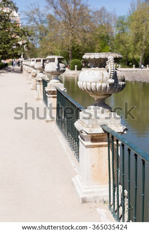 Stone jars over a railing near a river