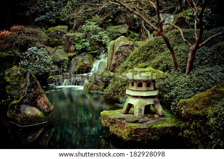 Stone lantern on a koi pond with a small waterfall. - stock photo