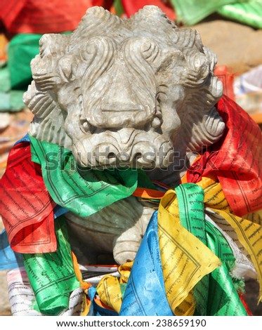 Stone lion figure with traditional buddhist prayer flags in lamasery, Inner Mongolia - stock photo