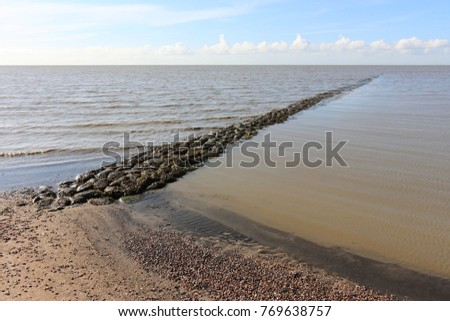 Stone made breakwater or wave breaker in the Wadden Sea in The Netherlands at low tide with brown water and a blue sky