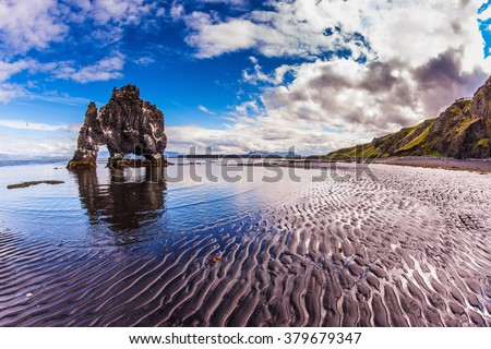 "Stone ""mammoth"" Iceland. The picturesque cliff in Bay of Hoonah during low tide at sunset"