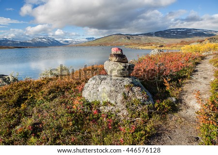 Stone marked hiking sign in Norway on Cunojavri - stock photo