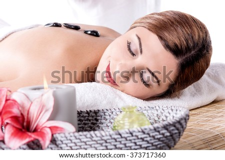Stone massage for young woman at beauty spa salon - stock photo