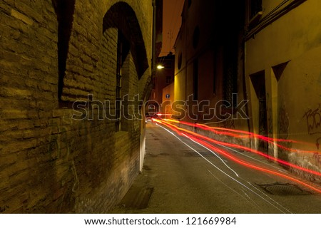 stone medieval street in Bologna and car red headlights at night, Italy - stock photo