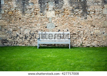 Stone medieval wall with a wooden blue bench, France, Europe - stock photo