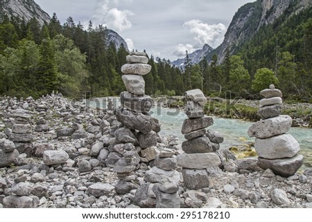 Stone men at the young Isar in Hinterautal valley - stock photo