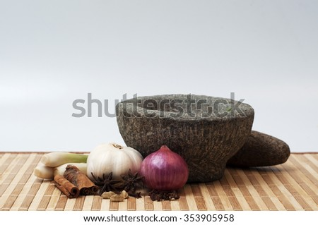 stone mortar and pestle with red onion,garlic, herbs - stock photo