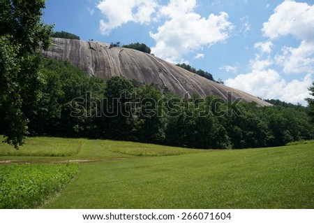 Stone mountain behind field