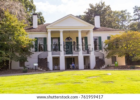 STONE MOUNTAIN, GA - SEPT 25, 2017: Woman relaxing in front of historic Davis House in Stone Mountain Park. Considered excellent example of neoclassical architecture.