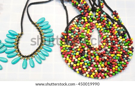 Stone necklaces. Beautiful pattern of colorful necklaces made from natural stone. Colorful bead and stone necklaces showcased on white table background for sale at  jewelry store - stock photo