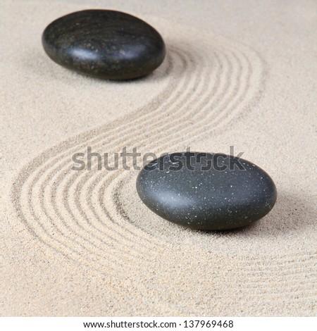 Stone on raked sand - stock photo