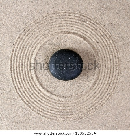 Stone on raked sand - stock photo