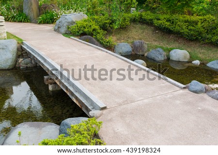 stone path in a japanese garden stone bridge across a tranquil pond