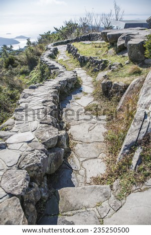 Stone path road and wall in the field. - stock photo
