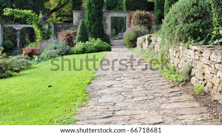 Stone Pathway in a Peaceful Green Garden - stock photo