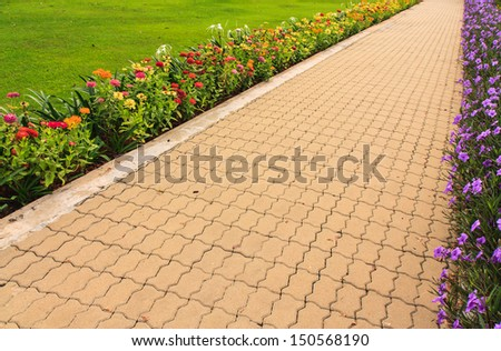 Stone pathway in garden with flower on both side - stock photo