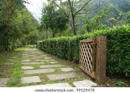 Stone pathway in garden with open wood door at Taroko National Park - stock photo