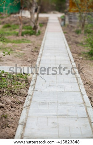 Stone pathway into garden during day time . Outdoor. Summer. - stock photo