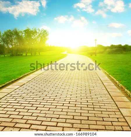 Stone pathway under sunlight in the park. - stock photo