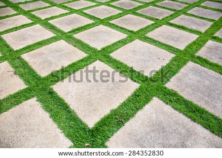 Stone pathway with grass in a green garden - stock photo