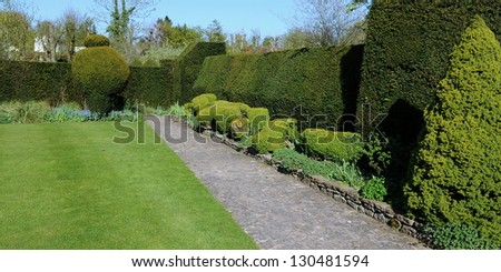 Stone Pave Pathway and Topiary in a Landscape Garden - stock photo