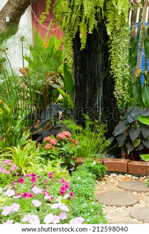 Stone Paved Garden Path with a Lawn and Flowerbed - stock photo