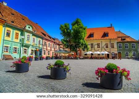 Stone paved old street with cafe bar in city center,Sighisoara fortress,Transylvania,Romania,Europe - stock photo
