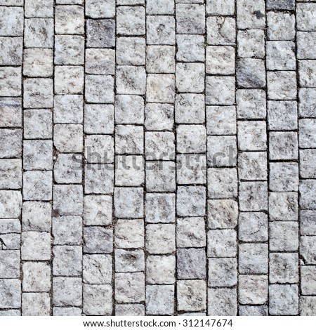 Stone pavement texture. Granite cobble stoned pavement background. Abstract background of old cobblestone pavement close-up. - stock photo