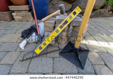 Stone Pavers for backyard patio hardscape with garden landscaping tools gloves level rubber mallet sand gravel tamper rake - stock photo