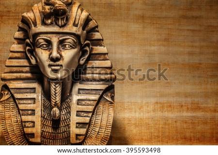 Stone pharaoh tutankhamen mask on papyrus background - stock photo