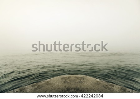 Stone pier in thick fog mystic. Toned image. - stock photo