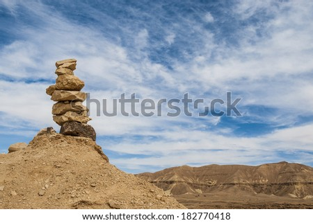 Stone pillar against a background of mountains in the desert.