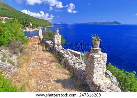 Stone pots on a fence above the shore of the Adriatic sea, Trsteno, Croatia - stock photo