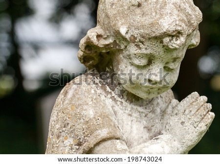 Stone praying child (close-up) - stock photo