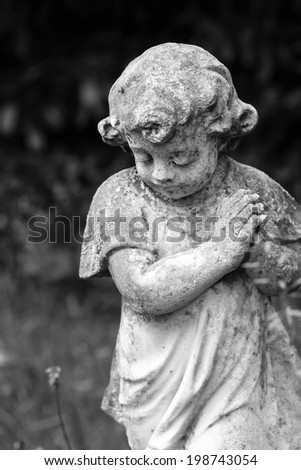 Stone praying child in black & white - stock photo
