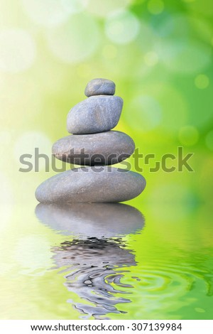 stone pyramid with green bokeh or Rocks isolated on white inside studio close up. Spa concept - stock photo