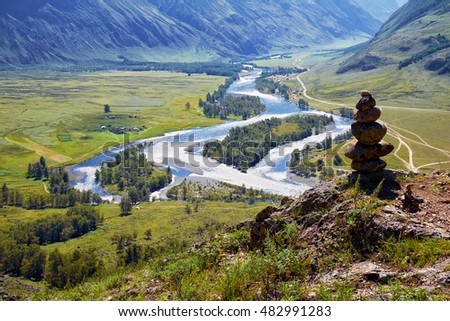 Stone pyramide in Altai mountains over river Chulyshman valley. Siberia, Russia