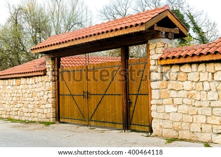 stone railing and gates from tree - stock photo