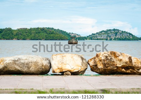 stone row foreground and focuses on founder boat at the beach on coast of phuket, Thailand - stock photo
