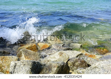 Stone,sand,sea water and beach with lighting in the morning:Close up,select focus with shallow depth of field:ideal use for background. - stock photo