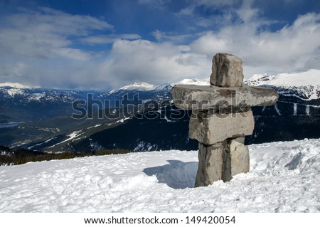 Stone sculpture Inukshuk stands prominently looking over the mountains and valleys atop Whistler Mountain, Canada - stock photo
