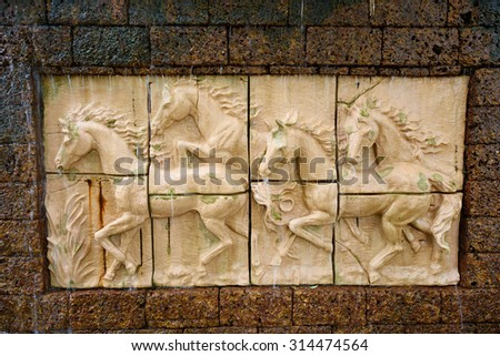 Stone sculpture of horse on brick wall with waterfall - stock photo