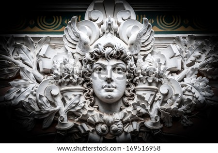 Stone sculpture showing head of man with curly hair surrounded by leaves of tree. Serious confident male face with angry look. Yellow and green wall in background. Symmetrical classical monument. - stock photo