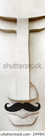 Stone sculpture with large false mustache like a hipster - stock photo