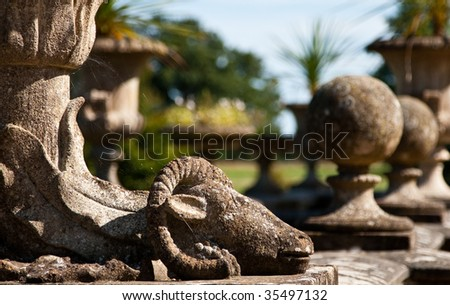 Stone sculpure of a ram at the base of a pot, in the royal gardens of Osborne House, located in Isle of Wight, UK