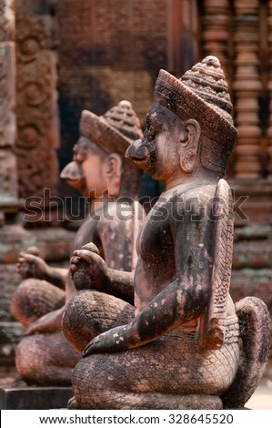 Stone sculputure sitting in front of temple Banteay Srei Angkor Wat - stock photo